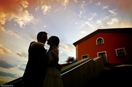 Novios abrazados a contraluz, al fondo hotel Qgat