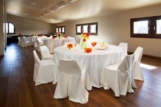 Sala Gausac con mesa preparadas con manteles blancos.