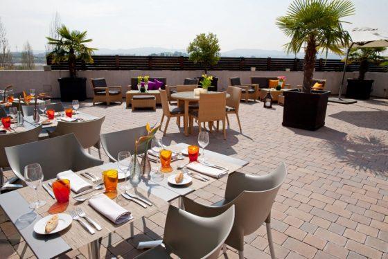 Terraza restaurante con mesas preparadas para comer en exterior