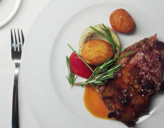 Carne con salsa y croquetas