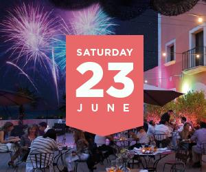 Terraza con personas cenando y fuegos artificiales